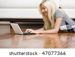 Smiling woman stretches out on the living room floor with her laptop. Horizontal format. - stock photo