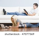 Man reads on a couch while woman stretches out on the floor with her laptop. Horizontal format. - stock photo