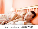 Man and woman sleep close together in a brightly-colored bedroom. Horizontal format. - stock photo