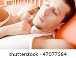 Cropped close-up of man and woman sleeping close together in bed. Horizontal format. - stock photo