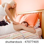 Cropped view of man lying on bed as woman massages his back. Square format. - stock photo