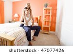Smiling woman hugs man as they sit on their bed together. Horizontal format. - stock photo