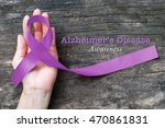 Small photo of Alzheimer's Disease (AD) Awareness with purple ribbon (clipping path) on helping hand support for World Alzheimers day (month) concept