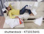Stock photo procrastination man lying on the sofa he does not want to work working papers flying in all 471015641