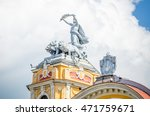 Small photo of Statue on allegorical car pulled by lions on a tower at the Cuj-Napoca National Theater and Opera House in the Transylvania region of Romania. A baroque rococo building in a close view
