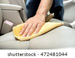 A man cleaning leather car seat with microfiber cloth - auto detailing and valeting concept - stock photo