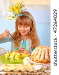 young girl painting easter eggs by the table - stock photo