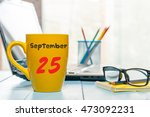 Small photo of September 25th. Day 25 of month, calendar on green tea cup at Administrator workplace background. Autumn time. Empty space for text