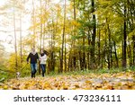 Stock photo beautiful young couple with dog running in autumn forest 473236111