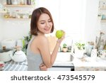 happy young asian woman eating... | Shutterstock . vector #473545579