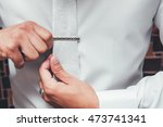 man in white shirt putting on... | Shutterstock . vector #473741341