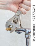 Small photo of Close-up of plumber hands screwing faucet valve using plumbers adjustable spanner.
