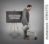 Small photo of Advertising campaign text on blackboard with businessman