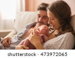 Small photo of Portrait of a young family. mom, dad and newborn baby resting at home