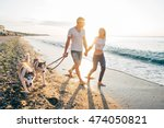 Stock photo young caucasian couple walking on beach with siberian husky dogs 474050821