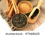 green tea, brown sugar and cinnamon on fabric - stock photo