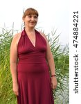 Small photo of The woman in a summer claret dress costs on the bank of a pond
