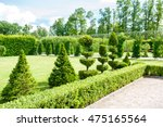 Round shaped topiary green trees with hedge on background in Rundale ornamental garden. latvia. Vibrant summertime outdoors horizontal image. - stock photo