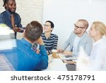 Small photo of Group of executives at conference table in office listening intently to lively charismatic Afro-American colleague presenting idea to them