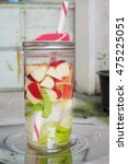 Small photo of How to make infused water from red apple, lime, mint leaf. Infused water is water that has fruit or herbs added to it. Gives the water a particular flavor and absorption of vitamins into the water.