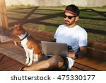 Stock photo a hipster in white unlabeled t shirt is working on his laptop in a city park in the company of his 475330177