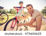 father is checking wheel of her ... | Shutterstock . vector #475604635