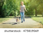 Stock photo young woman walking dog on walkway in park 475819069