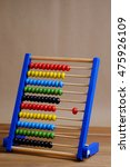 Small photo of Close up colorful abacus, traditional abacus in front of wooden background.