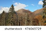 Autumn in the mountains, coniferous and deciduous trees, peaks in the haze of clouds, Caucasus, Russia - stock photo