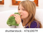 Young girl with blonde hair and purple dress sitting on sofa kissing a toy frog, selective focus on lips