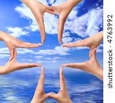 Conceptual cross symbol made from hands over blue seascape background - stock photo