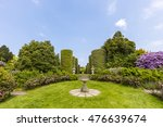 Stock photo english country garden with sundial and topiary shrubs 476639674