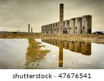 Small photo of Abandoned facility under moody cloudy dark sky, image of decrepitude