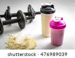 Stock photo fitness and workout concept with dumbbells protein shakers and a scoop in protein powder the two 476989039