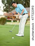 Fullbody young man outdoors playing golf hitting the ball - stock photo