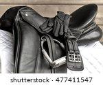 Small photo of Used black dressage horse riding saddle with girth, stirrup and riding gloves on white saddle pad
