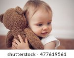 baby girl cuddling with a teddy ... | Shutterstock . vector #477619561