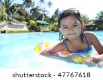 young asian girl enjoying at the swimming pool - stock photo