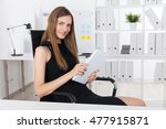 Small photo of Smiling business woman in black dress holding large tablet with both hands and smiling Mona Lisa smile to camera. Concept of your cunny colleague