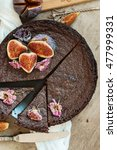 Small photo of ?hocolate ?ake with fresh figs and candied flowers on old wooden background, top view