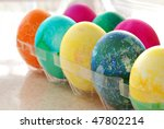 Colorful freshly dyed easter eggs in carton.  Sunny backlighting and extremely shallow dof.  Focus limited to blue egg. - stock photo