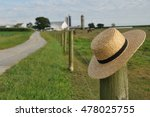 Small photo of closeup of Amish straw hat laying over farm fence post
