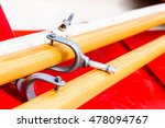Small photo of Close up and narrow focus on rowlock on wooden oar lying in red rowboat.