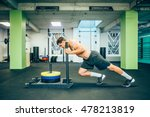 Muscular and strong young man pushing the exercise equipment at the gym