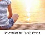 Young Woman Meditating On Beac...