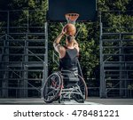 Small photo of Cripple basketball player in wheelchair plays basketball on open air ground.