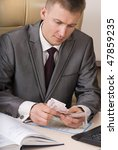 businessman counting ten euro banknotes sitting on the desk - stock photo