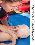 Small photo of Paramedic checking airways on an infant dummy doll during CPR training. Model is member of actual European first aid champions team for 2011/2012.