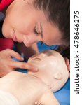 Small photo of CPR practitioner examining airway passages on infant dummy. Model is member of actual European first aid champions team for 2011/2012.