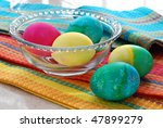 Colorful still life of freshly dyed easter eggs with brightly colored kitchen towels. - stock photo
